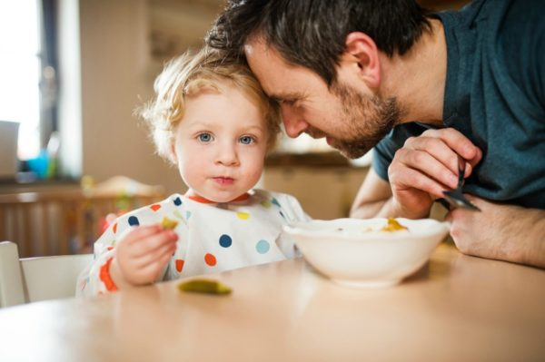 Toddler eating with dad