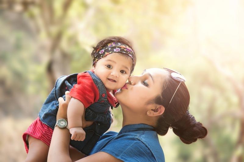 Mum kissing toddler at park