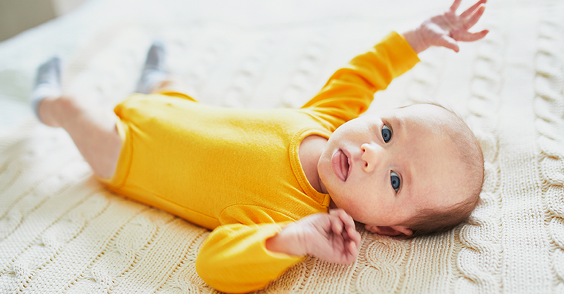 Newborn in yellow onesie