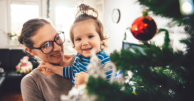 Mother holding child at Christmas tree