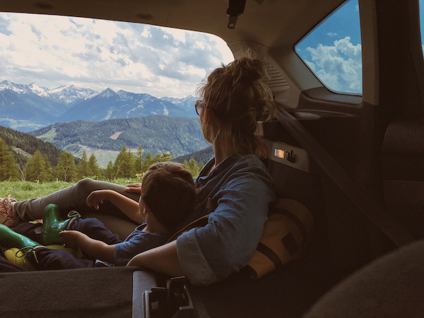 Mother and son enjoying the view of mountains from the car trunk