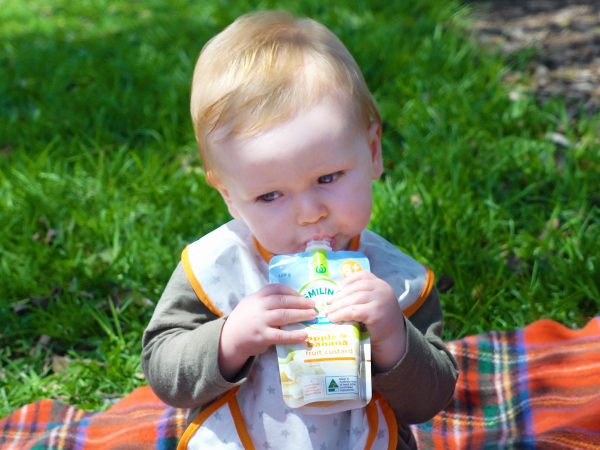 Baby eating from a Smiling Tums baby food pouch