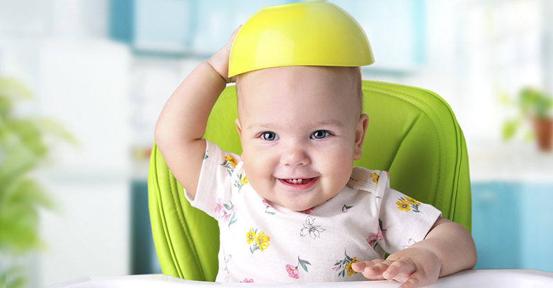 Baby sitting in a highchair with a bowl on his head