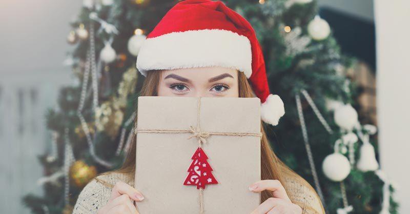 Woman wearing Santa hat holding gift