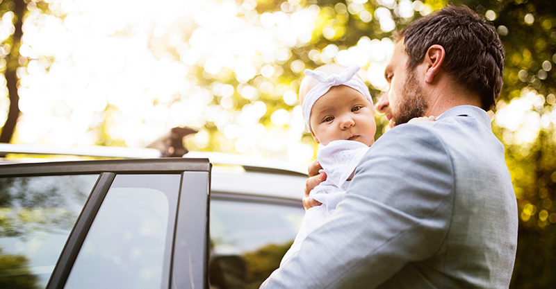 Dad putting baby in car