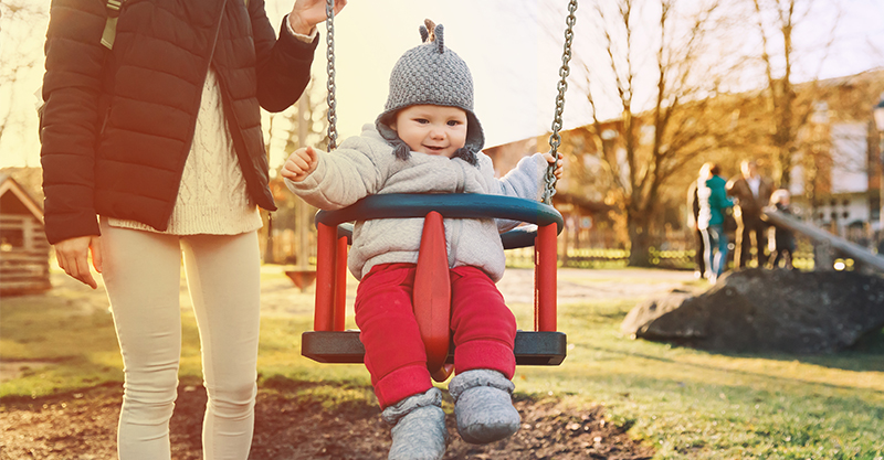 Mum at park with baby on swing